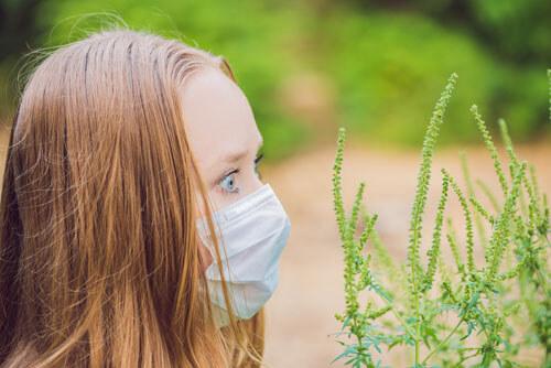 Junge Frau mit Allergie schaut verschreckt auf Graspollen.